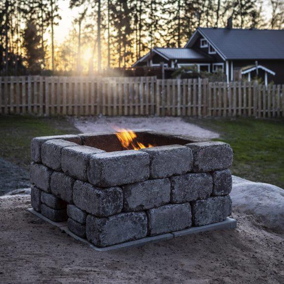 Firepit-tulisija harmaa, taustalla mökki